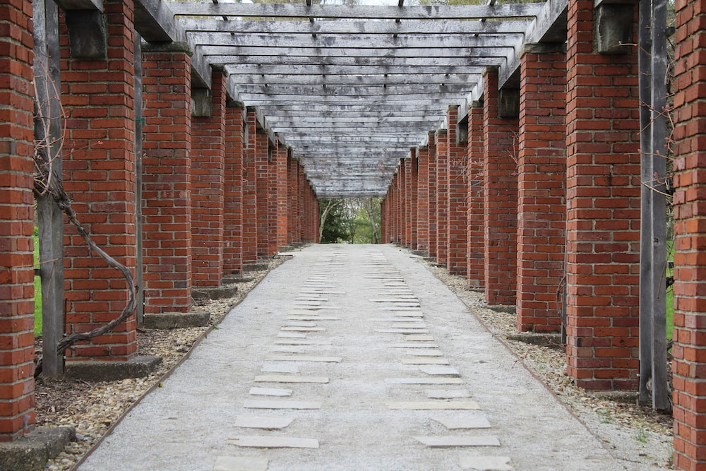 gray concrete pathway between red brick wall