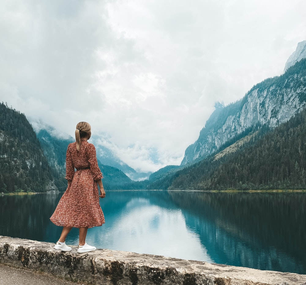 woman in red dress standing on rock near lake during daytime