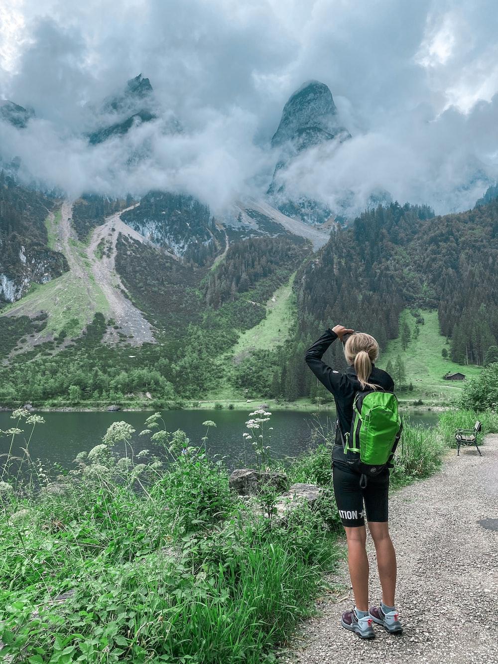 woman in green jacket standing near lake during daytime