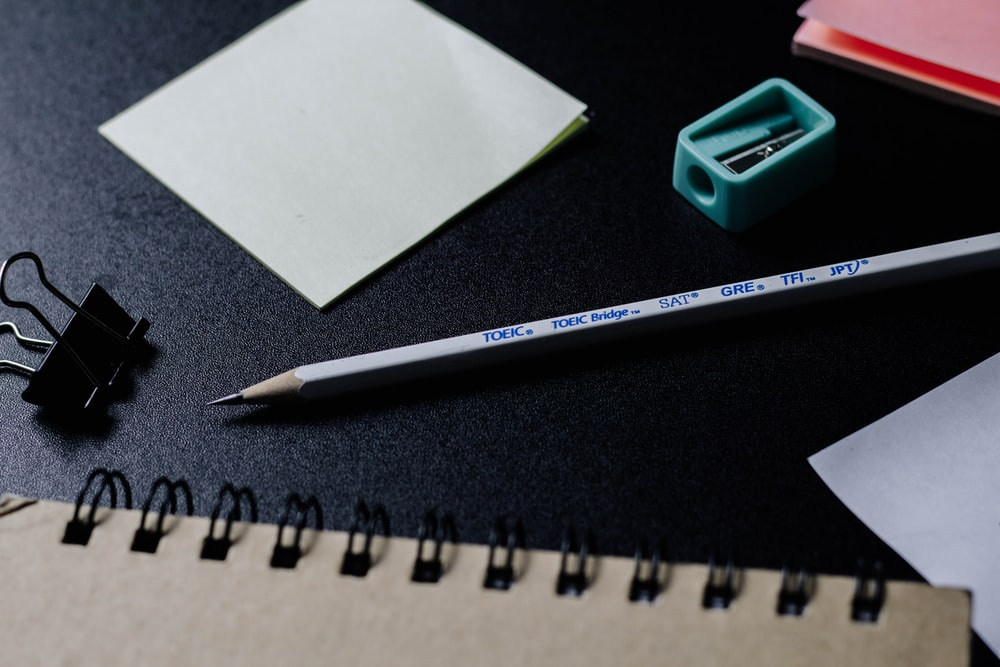 green pencil beside white paper