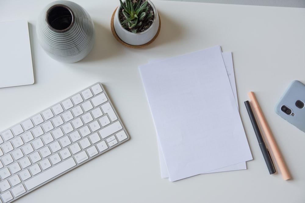white printer paper beside white apple keyboard