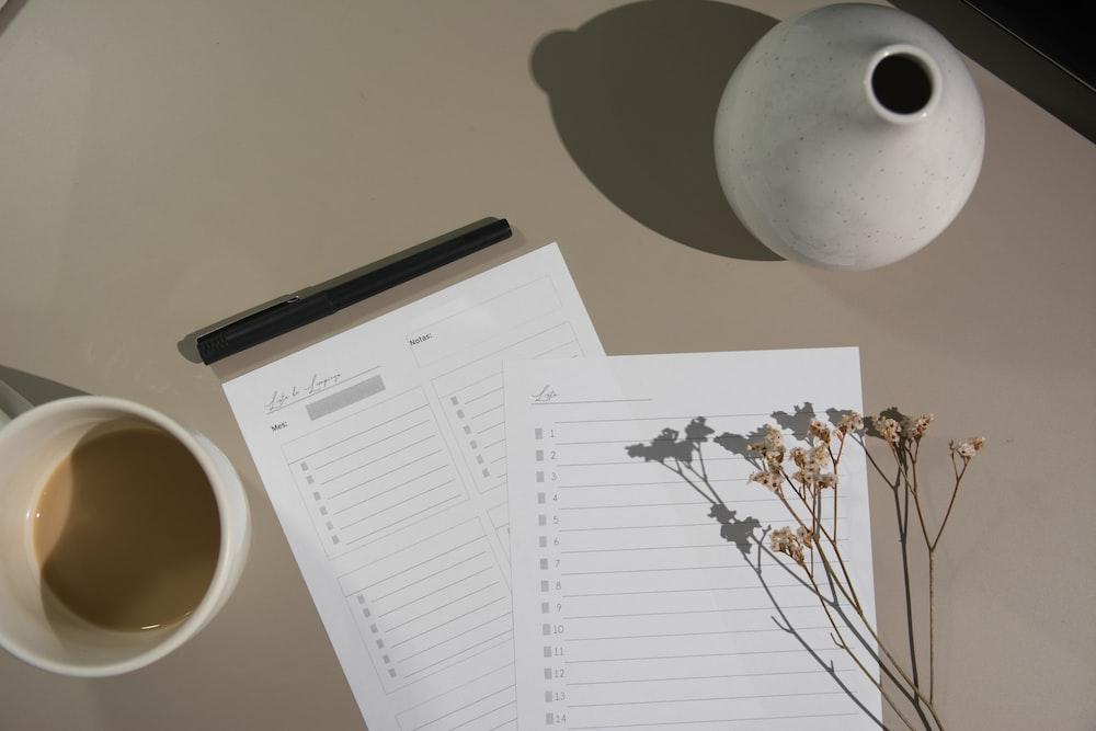 white printer paper beside white ceramic mug
