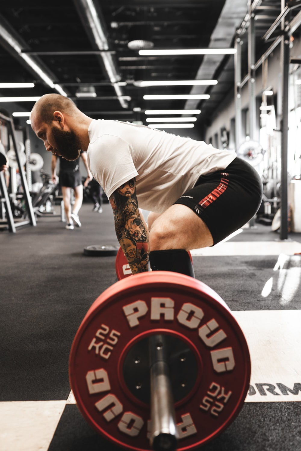 man in white t-shirt and black shorts carrying red and black barbell