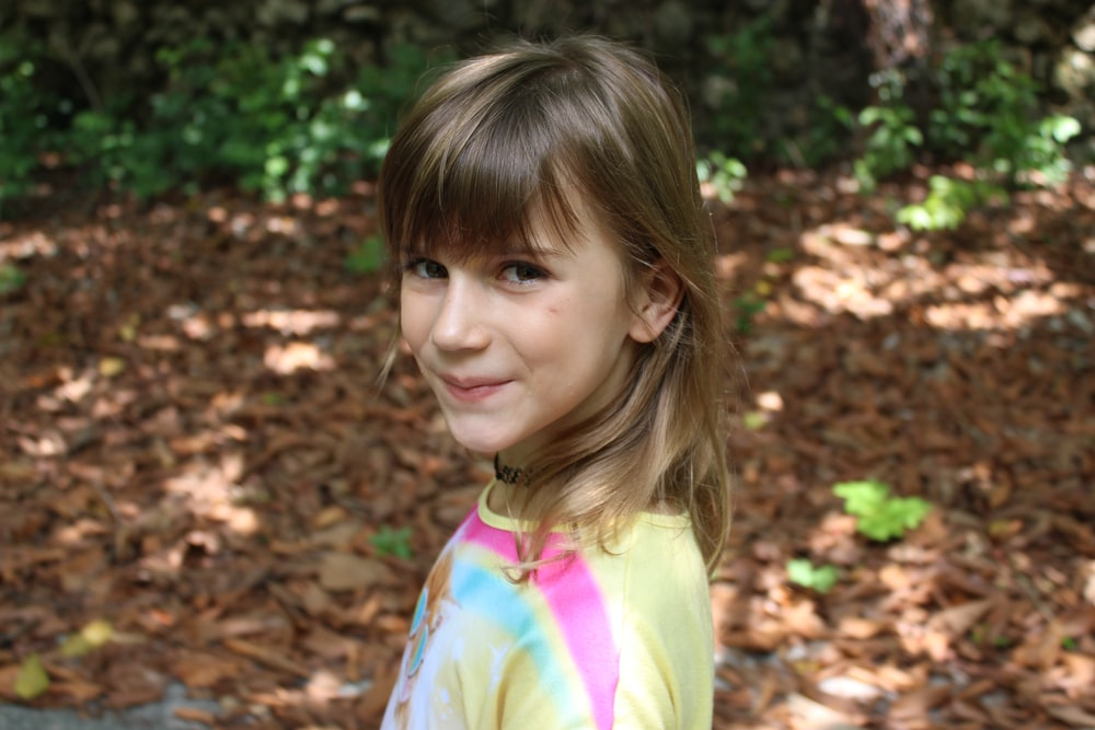 girl in yellow and pink shirt standing on brown leaves during daytime