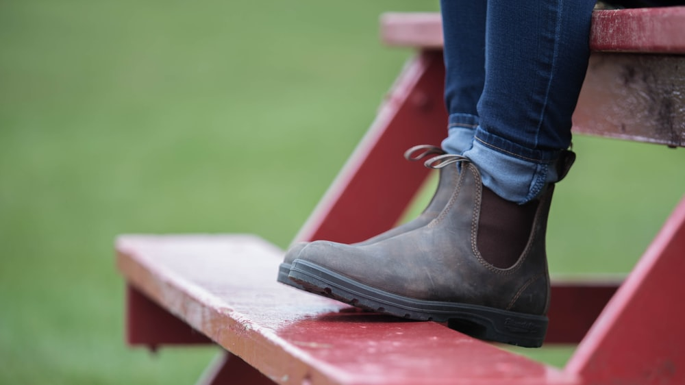 person wearing blue denim jeans and black leather boots sitting on red wooden bench