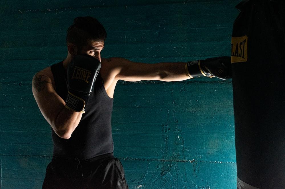 man in black tank top and black shorts wearing black boxing gloves