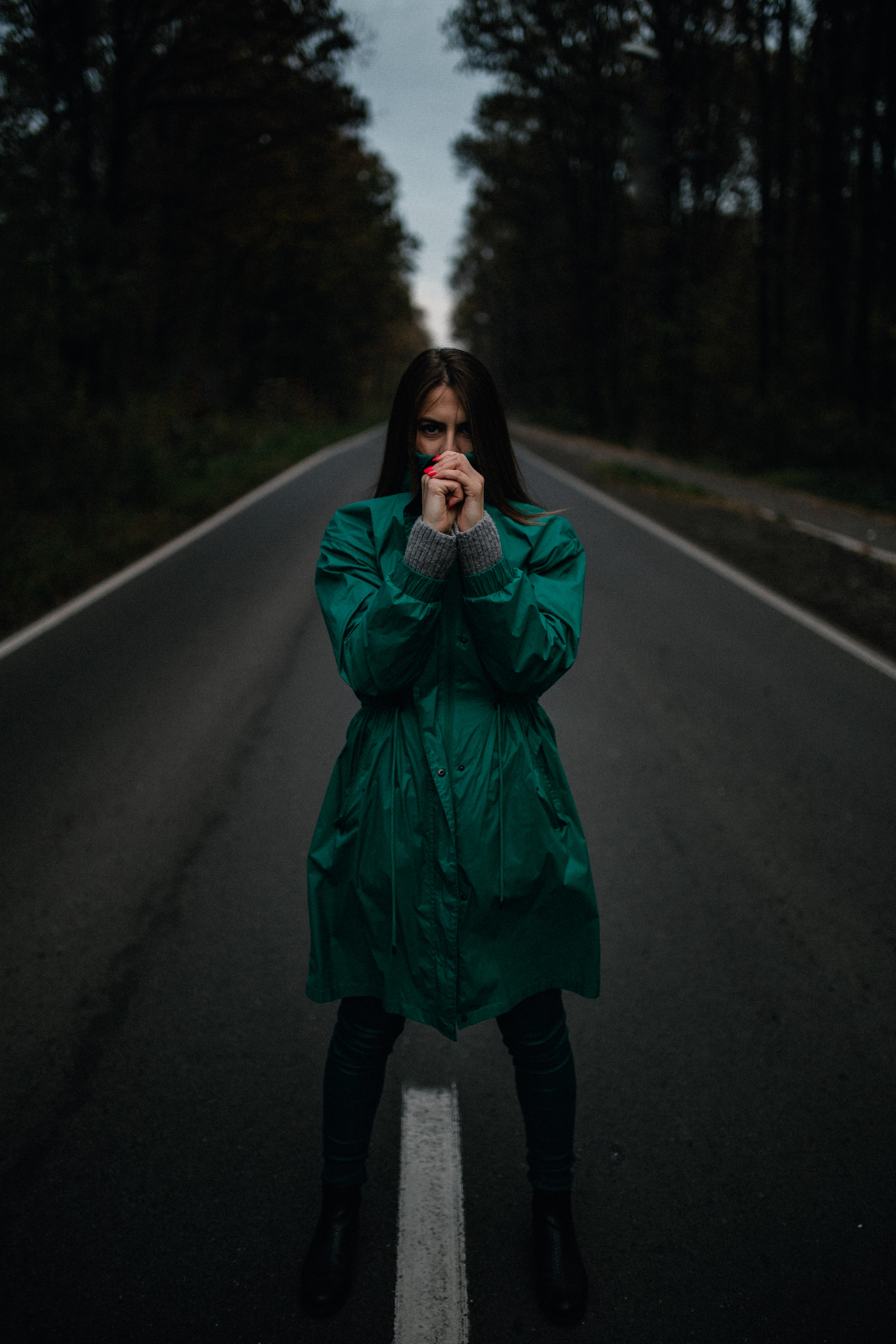 woman-in-green-coat-standing-on-road-during-daytime