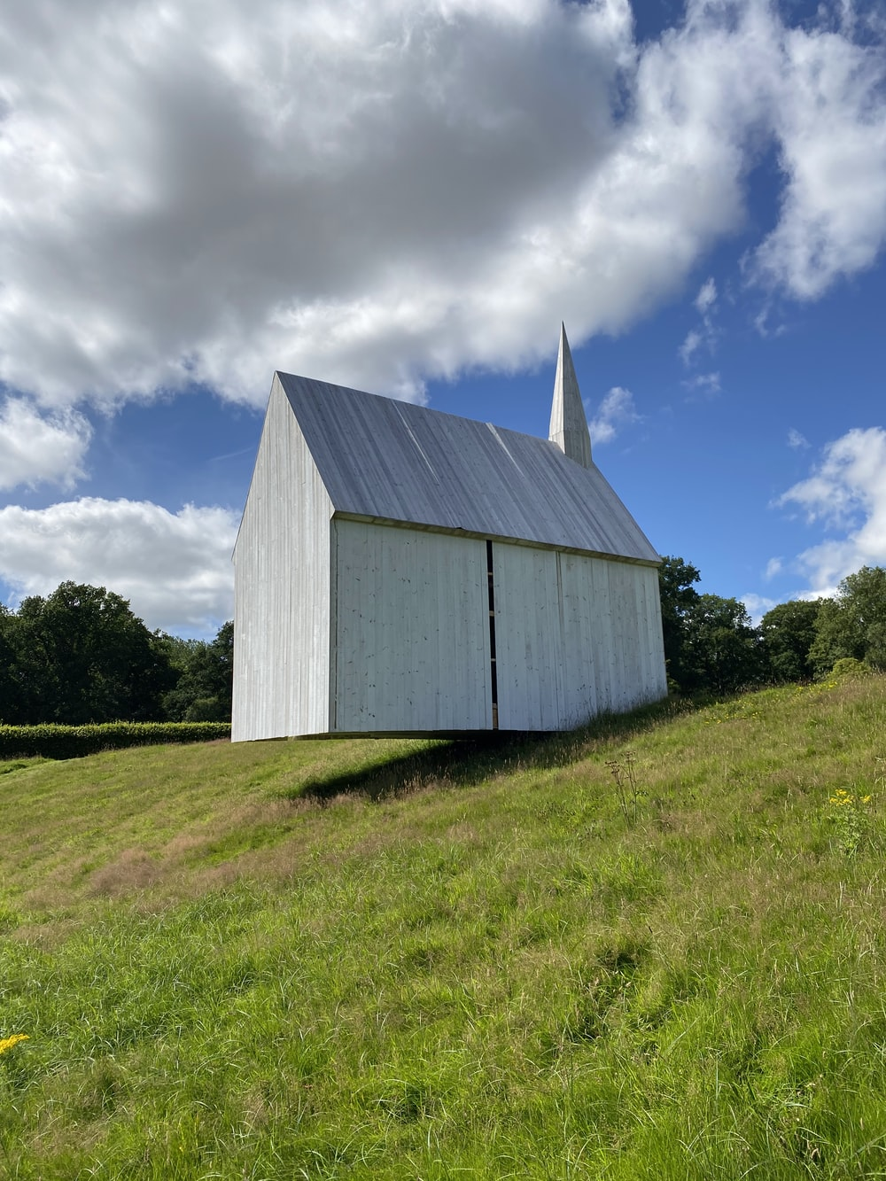 white wooden barn on green grass field under blue sky and white clouds during daytime