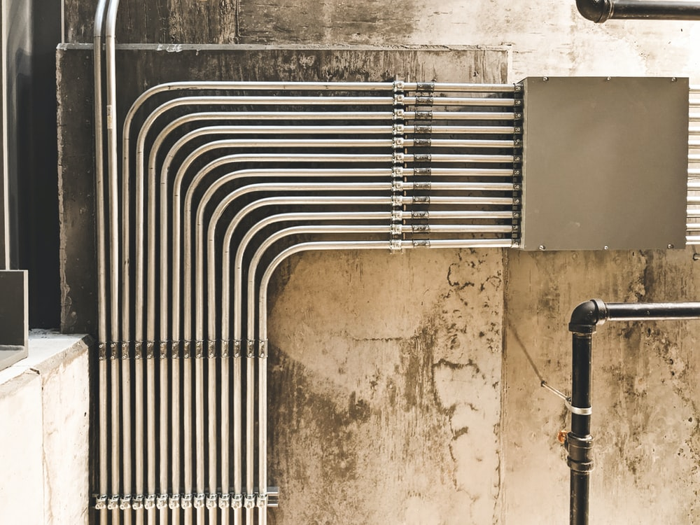 grey metal pipe on brown concrete wall