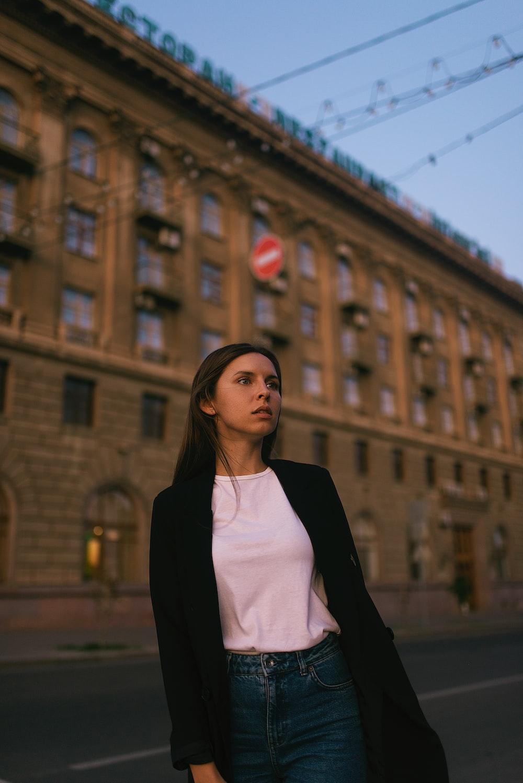 woman in black blazer standing near brown building during daytime