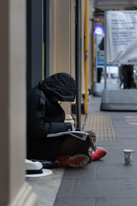 person in black hoodie sitting on sidewalk during daytime