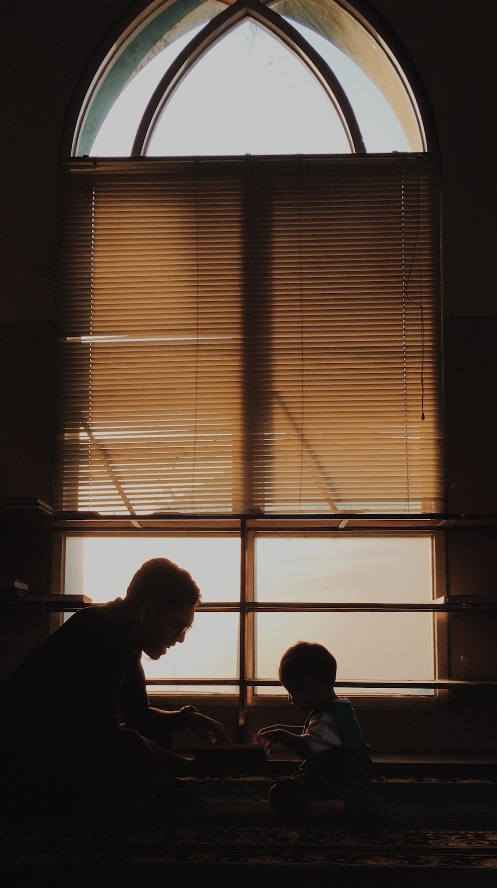 silhouette of man standing near window blinds
