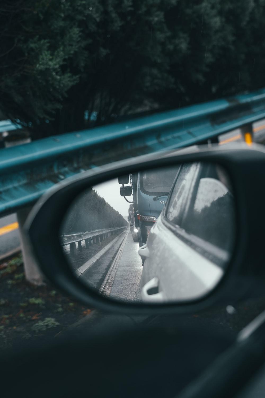 black car side mirror showing black car