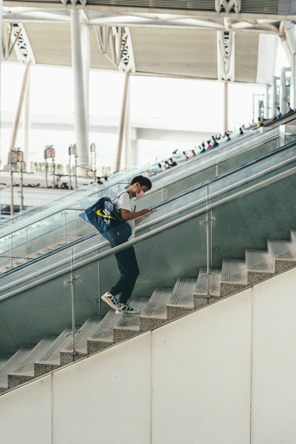 man in blue jacket and black pants on gray concrete staircase