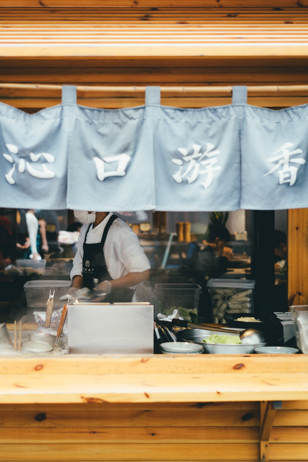 man in white apron standing in front of white table