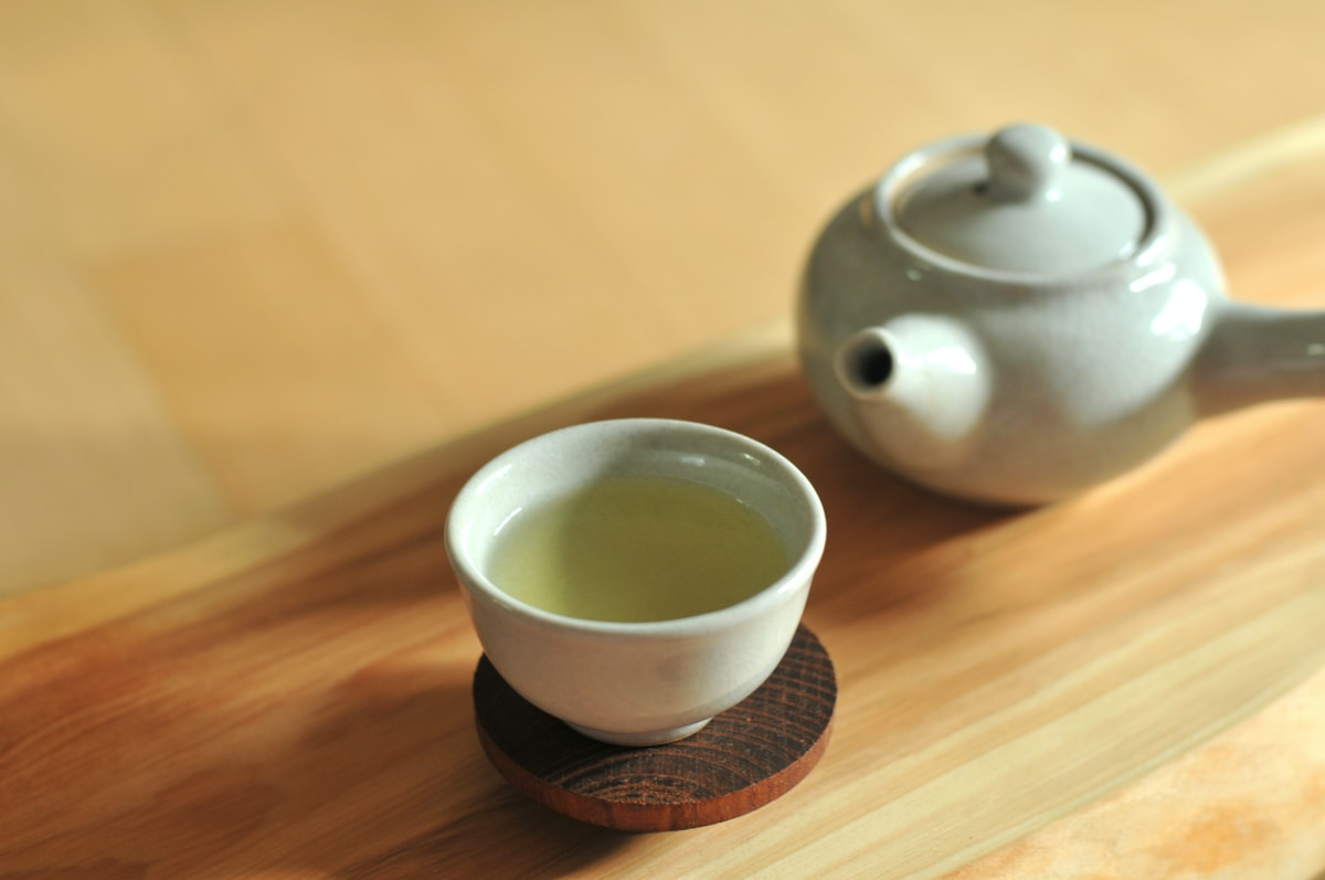 Simple tiny tea pot on a wooden table. There is a teacup filled with green tea on a wooden coaster.