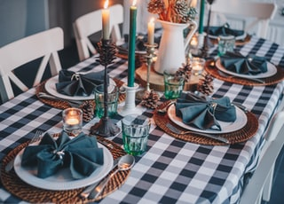 white candles on blue and white checkered table cloth