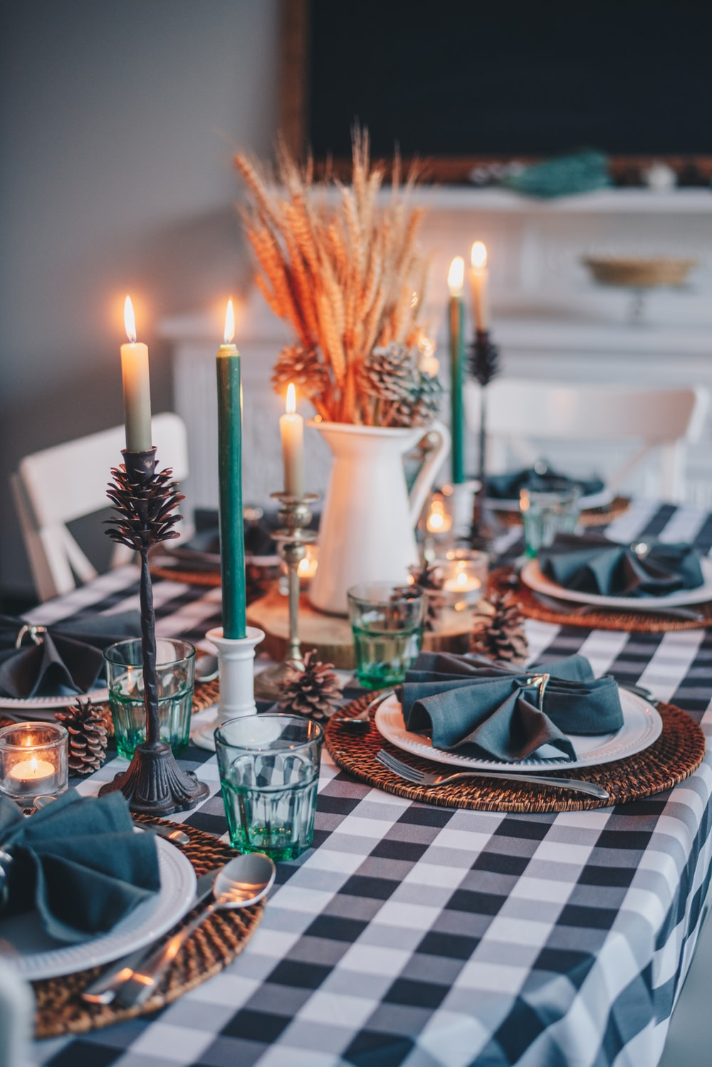 white candles on white and blue checkered table cloth