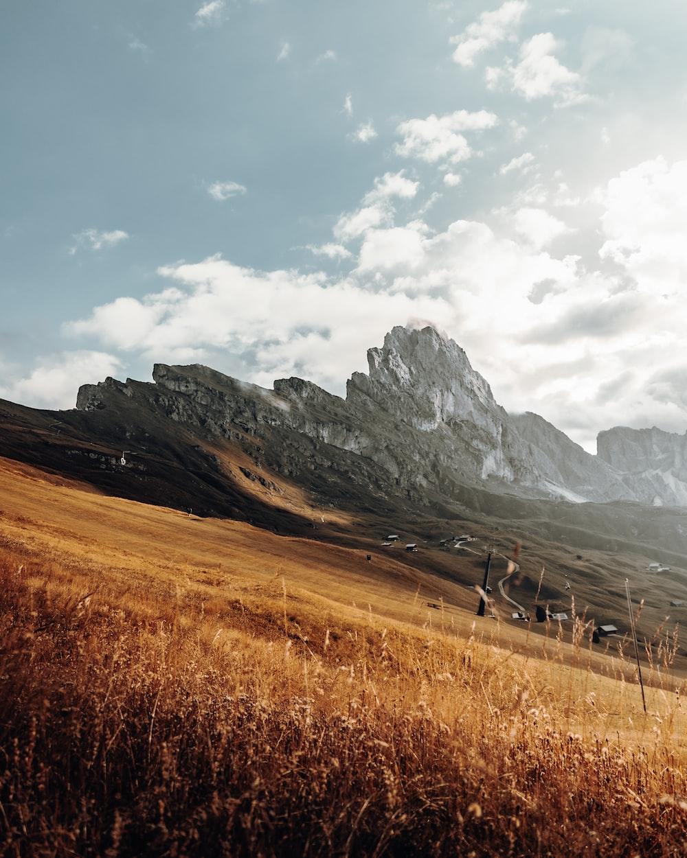 brown grass field near mountains under white clouds during daytime