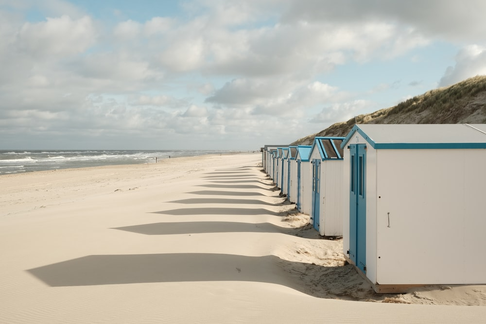 blue wooden shed on beach during daytime
