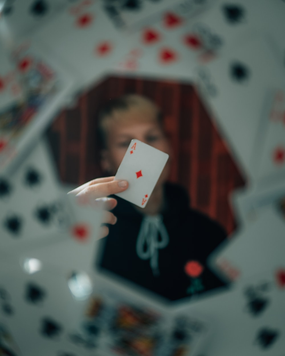 person holding 2 of diamonds playing card