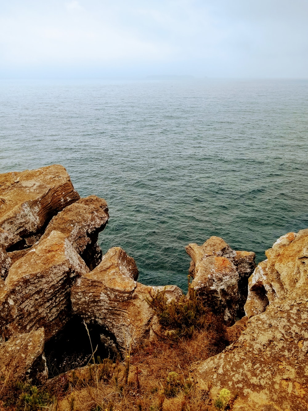brown rock formation beside body of water during daytime