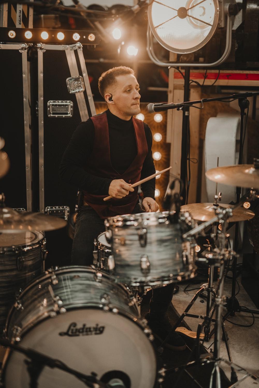 man in black long sleeve shirt playing drum