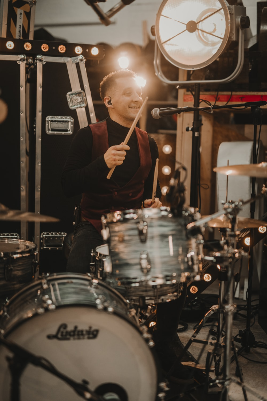 man in black crew neck t-shirt playing drum set