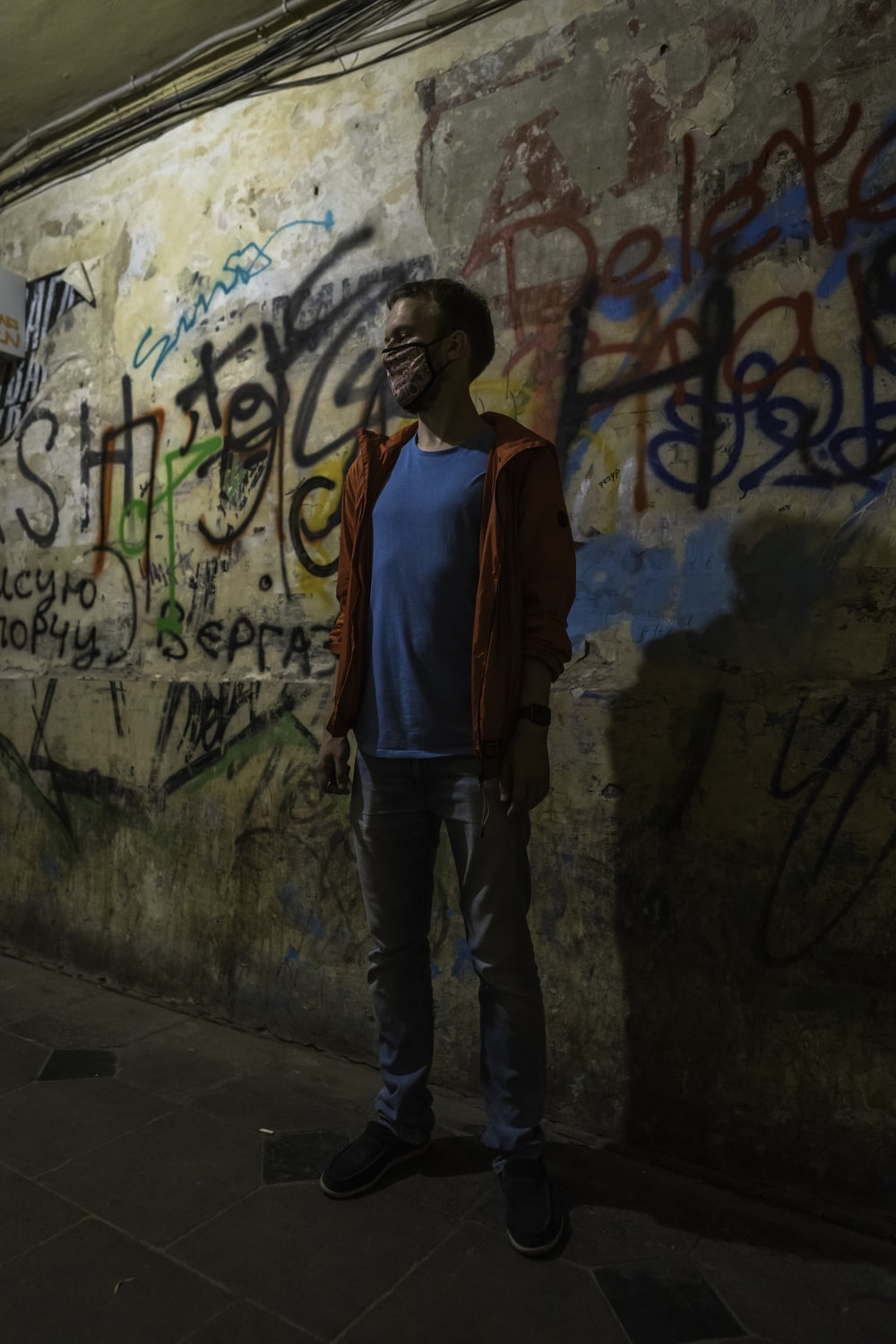 woman in red and blue jacket standing beside wall with graffiti