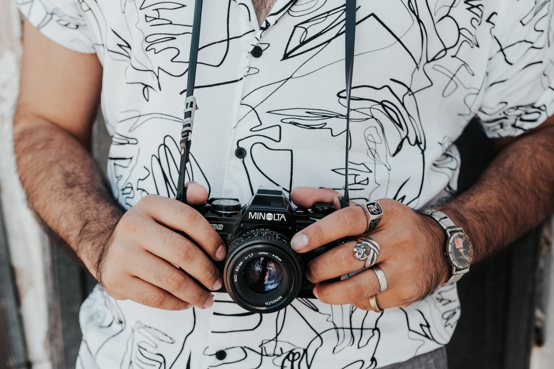 Man In White Button Up Shirt Holding Black Nikon Dslr Camera - unsplash