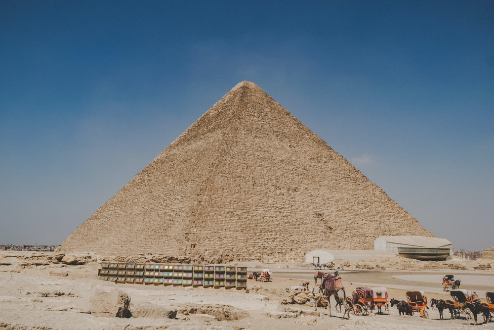 people walking on sand near pyramid during daytime