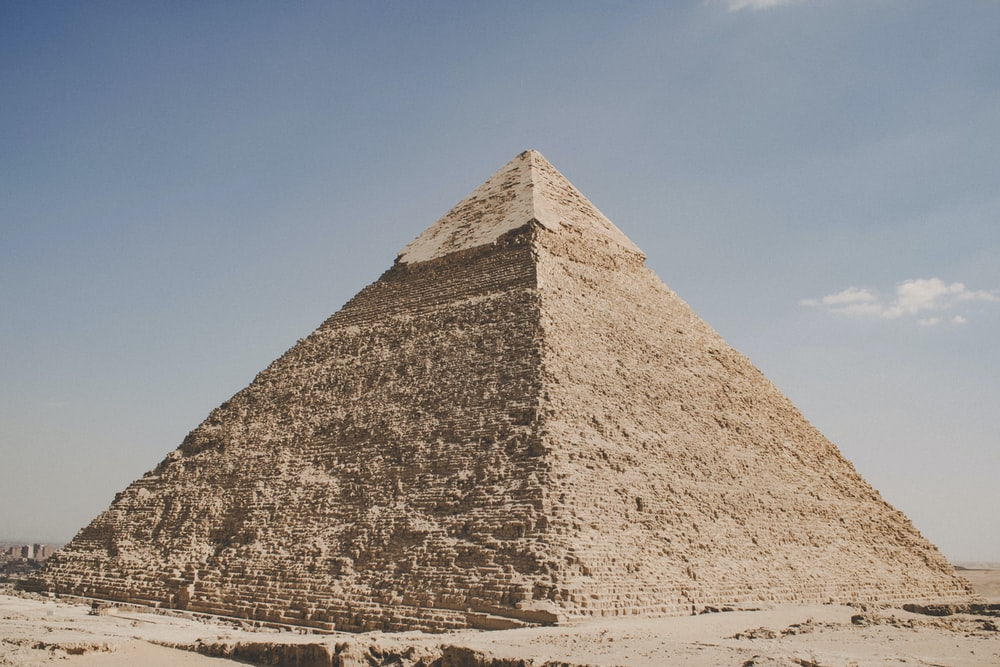 pyramid on brown sand under blue sky during daytime