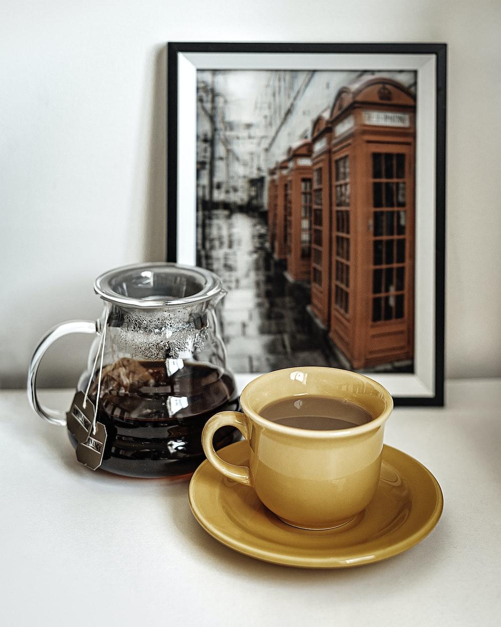 orange ceramic mug on saucer beside clear glass pitcher