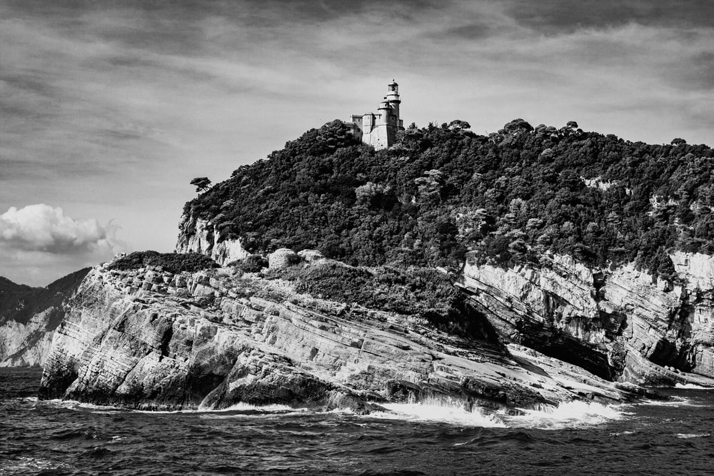 grayscale photo of lighthouse on rock formation