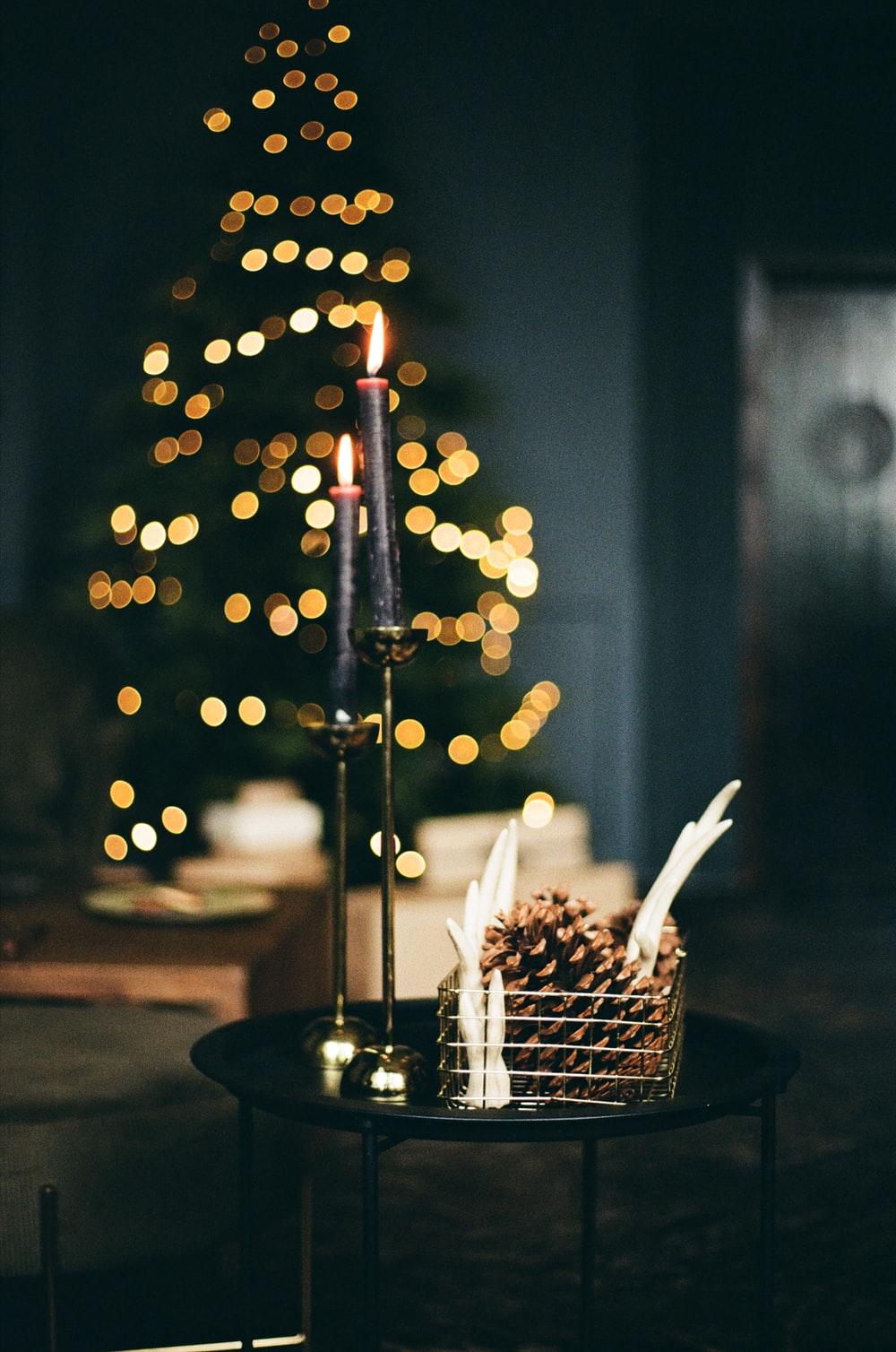 lighted candle on black metal holder