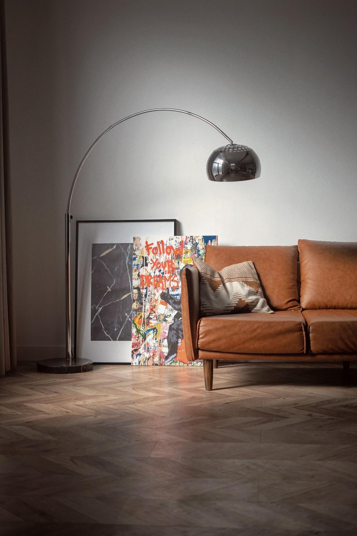brown wooden framed white padded armchair beside white wall
