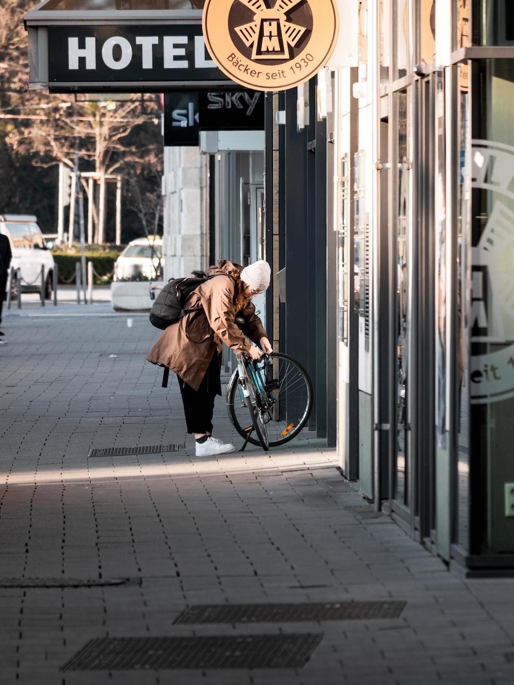 woman in brown coat and black pants walking on sidewalk during daytime
