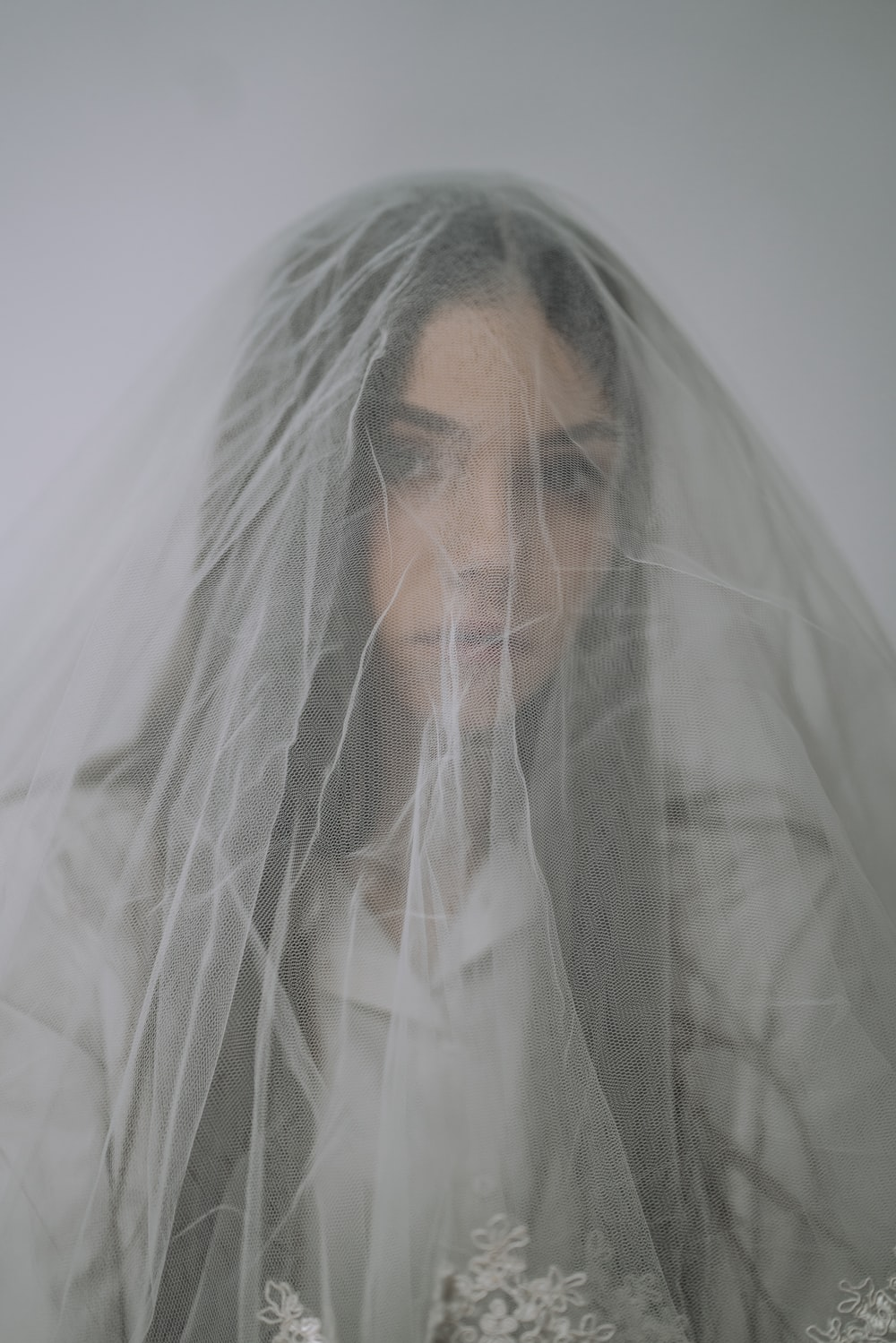 man in white veil covering his face with white textile