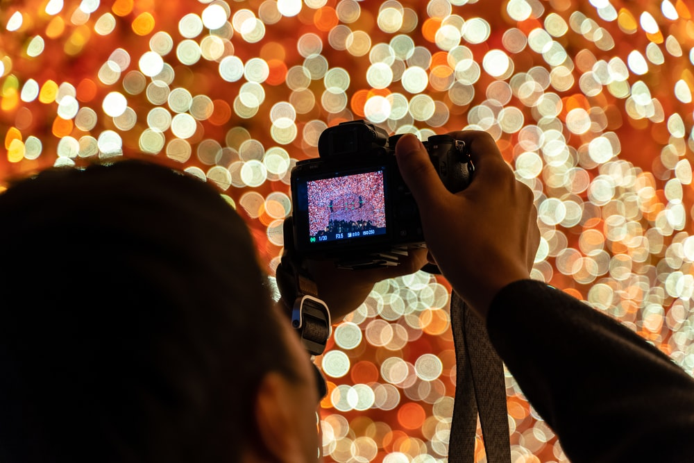 person holding black smartphone taking photo of lights