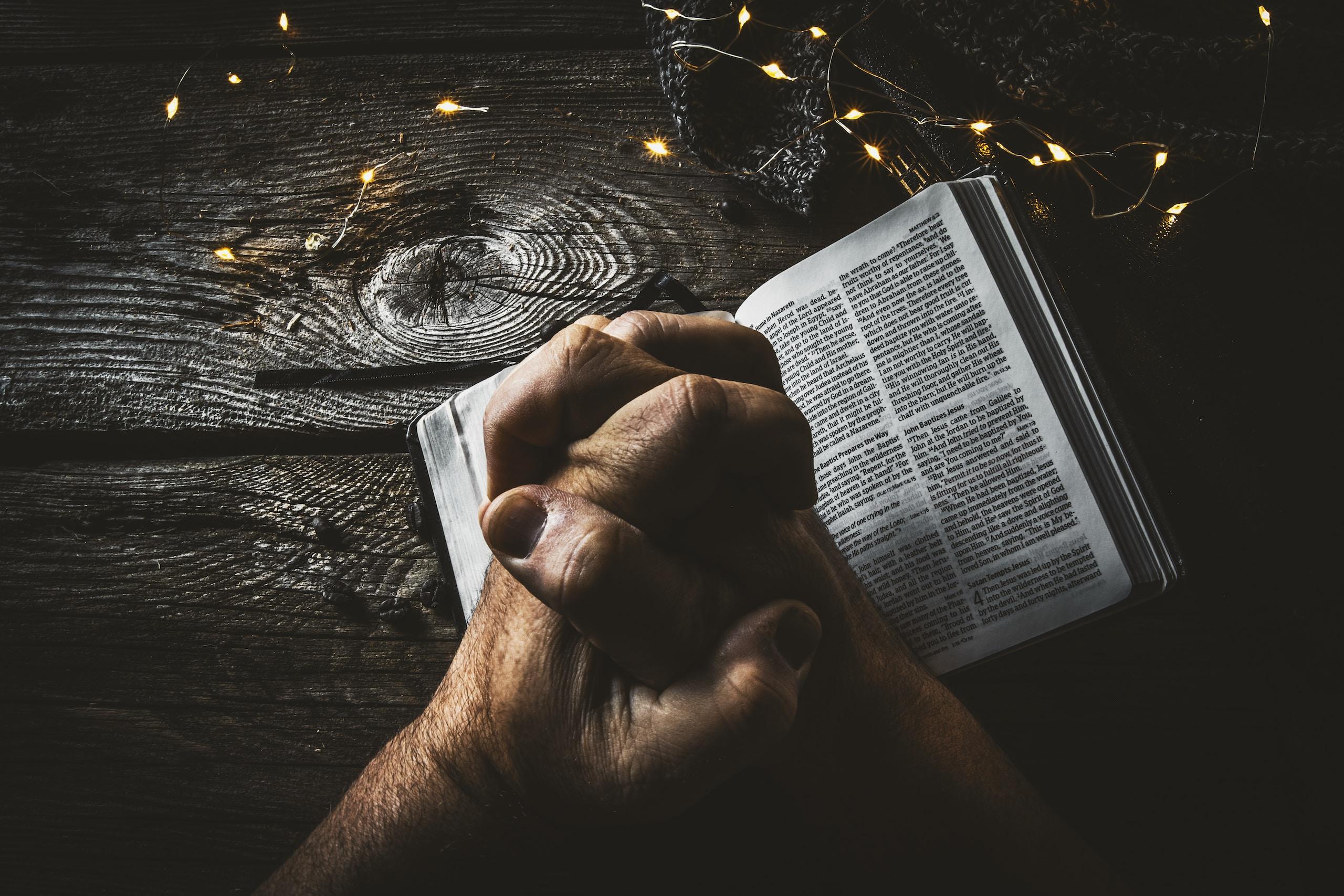 Man ber. Bibel ligger uppslagen på ett bord.