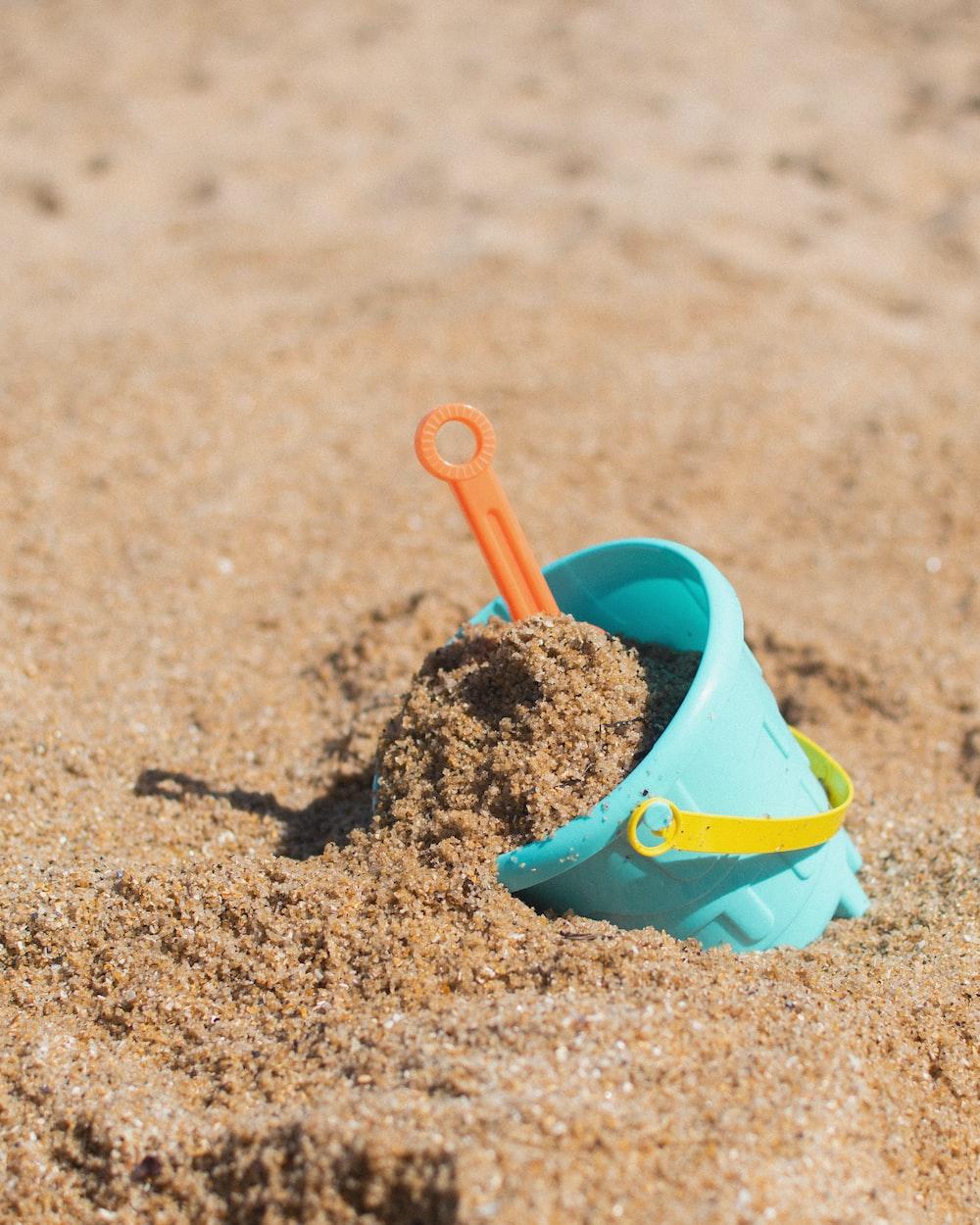 red plastic shovel on sand