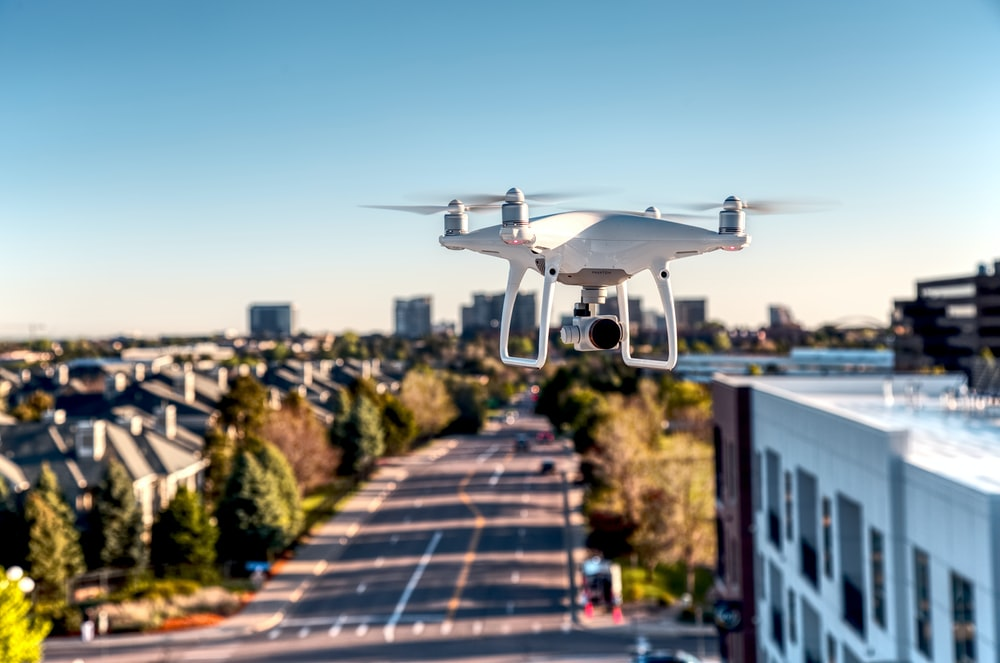 white drone flying over the city during daytime
