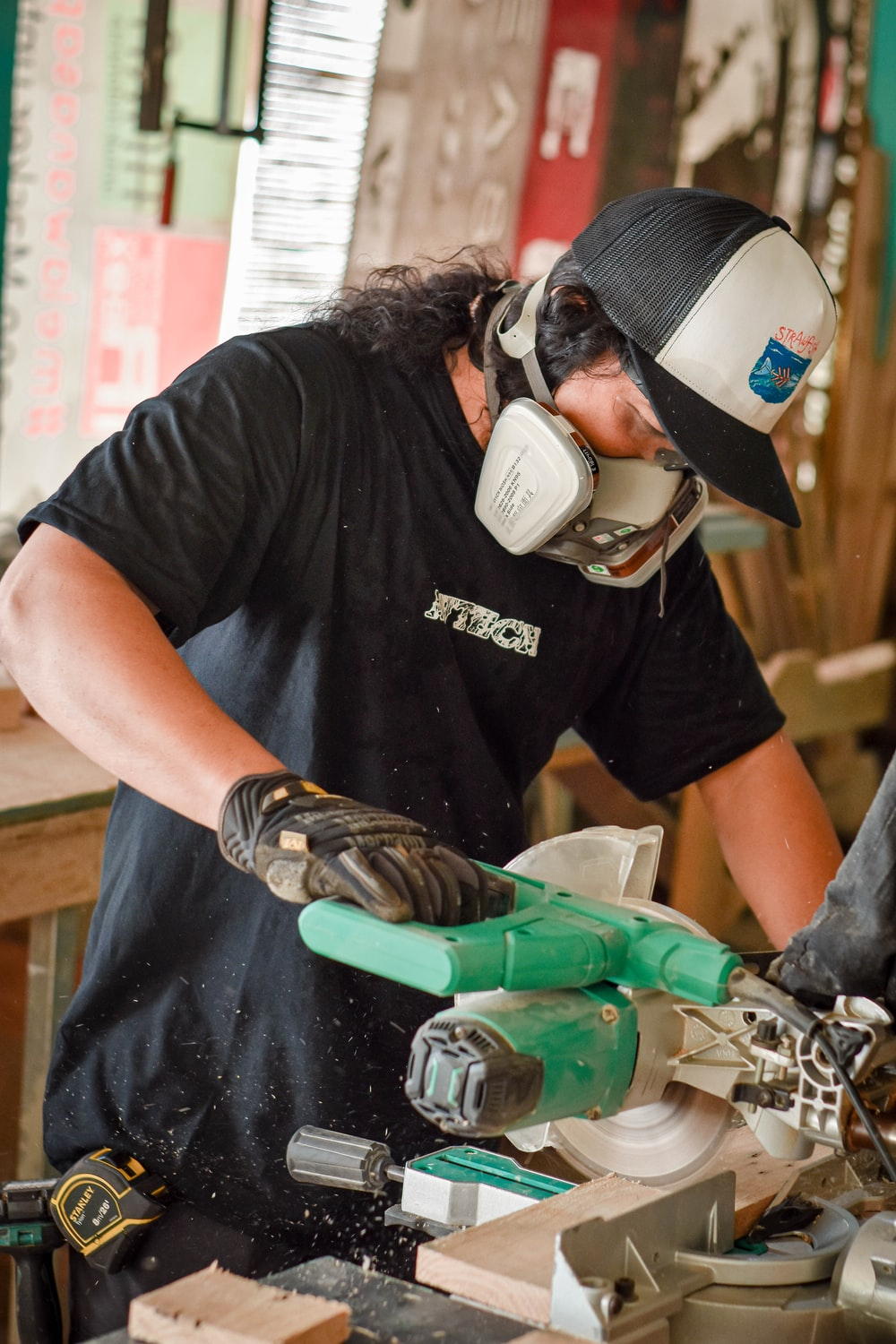 man in black crew neck t-shirt holding green and gray power tool