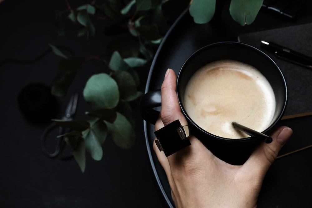 person holding black ceramic mug with brown liquid