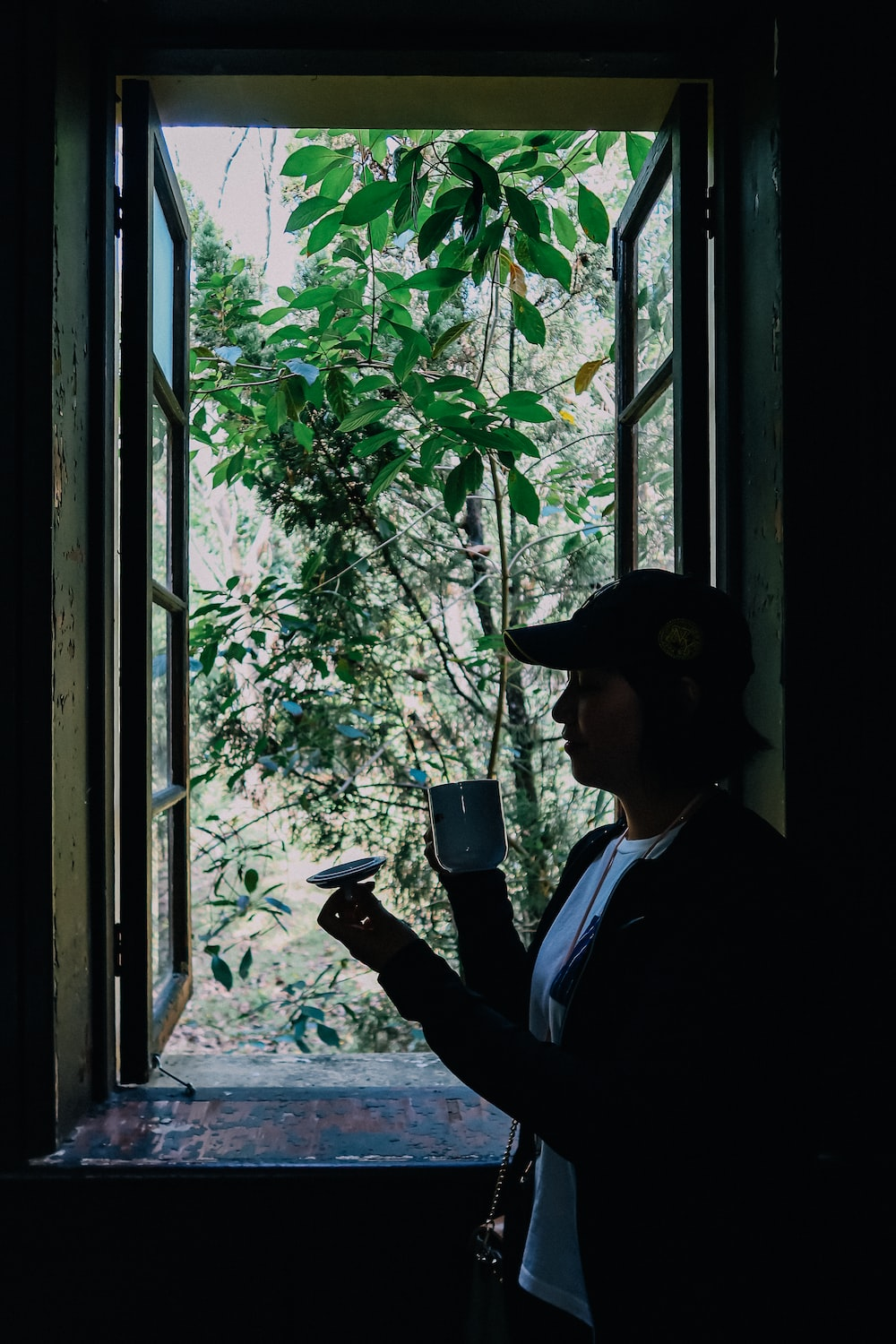 man in blue dress shirt and black fedora hat standing beside window