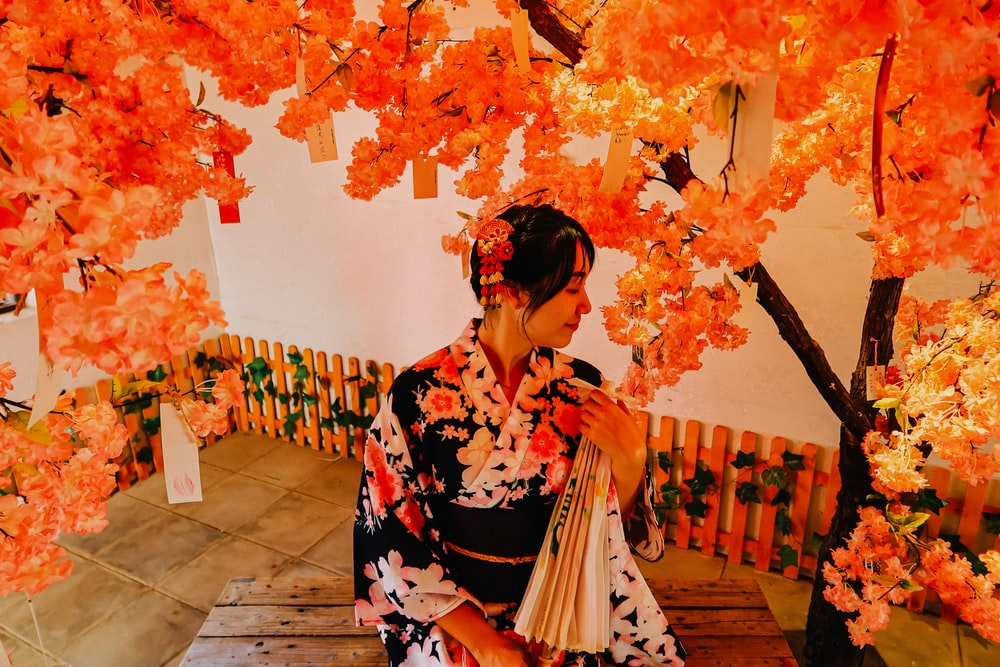 woman in black red and white floral kimono standing near brown wooden bench