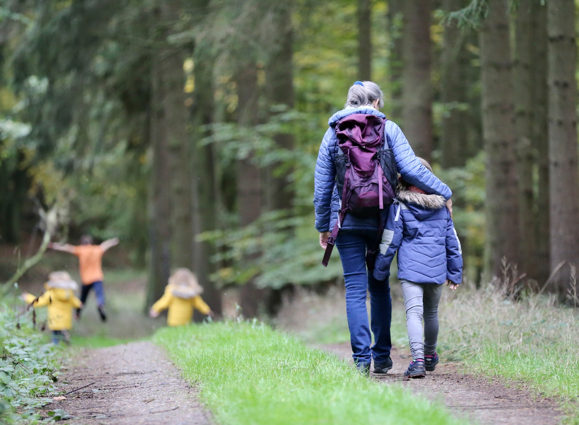 Grandmother with grandchildren hiking in a forest.