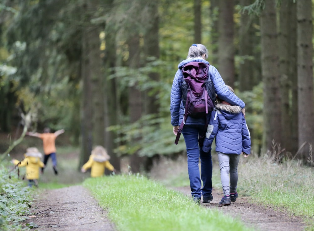 woman in blue denim jeans and black jacket walking with woman in green jacket