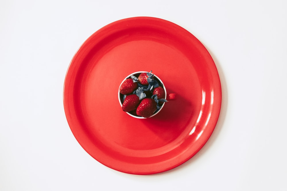 silver and red round ornament on red round plate