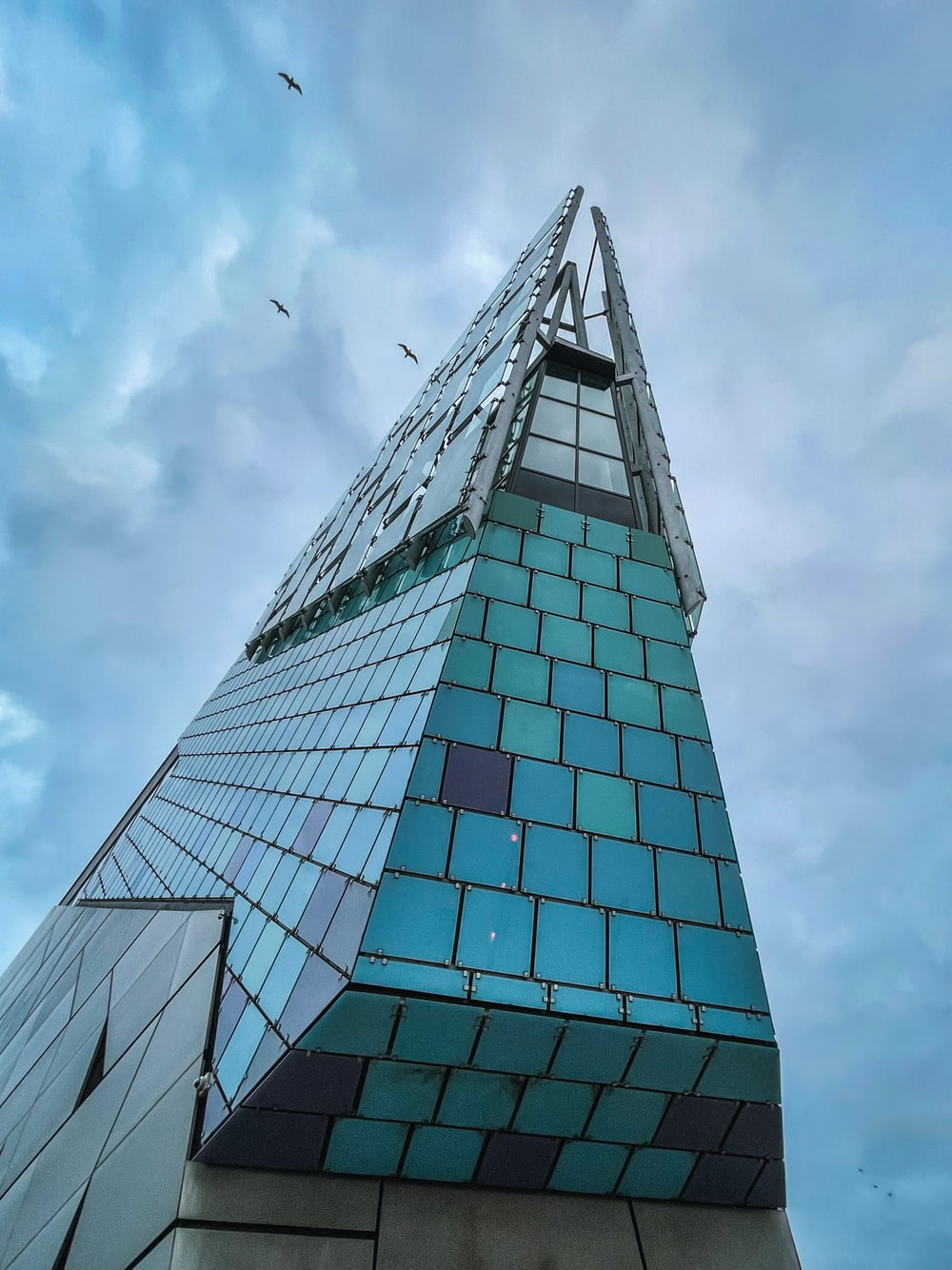 low angle photography of glass building under blue sky during daytime